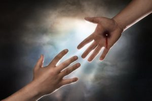 Hand of Christ reaching down from heaven to grab the hand of man